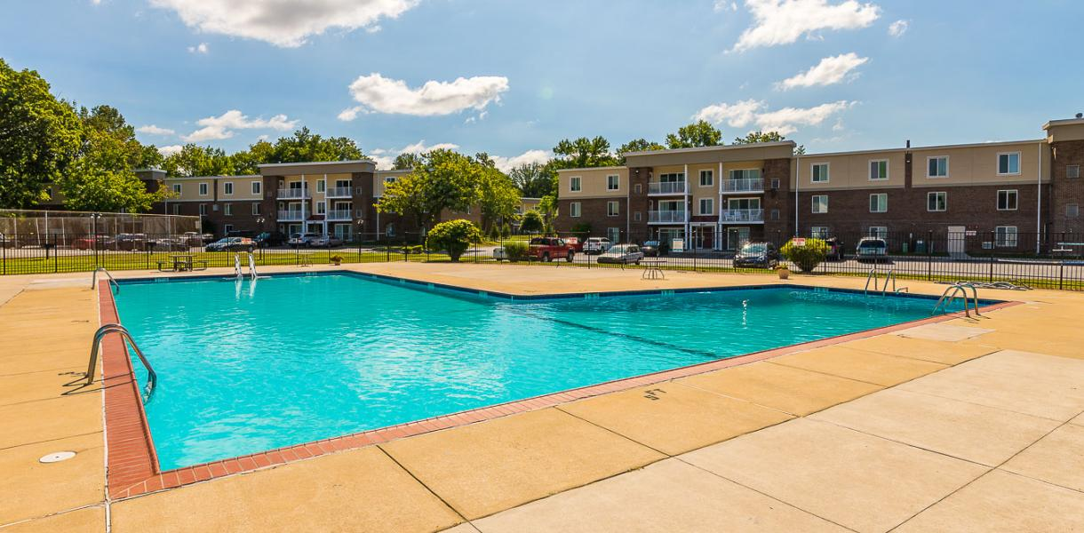 view of the pool with the Salem Village Apartment buildings in the background
