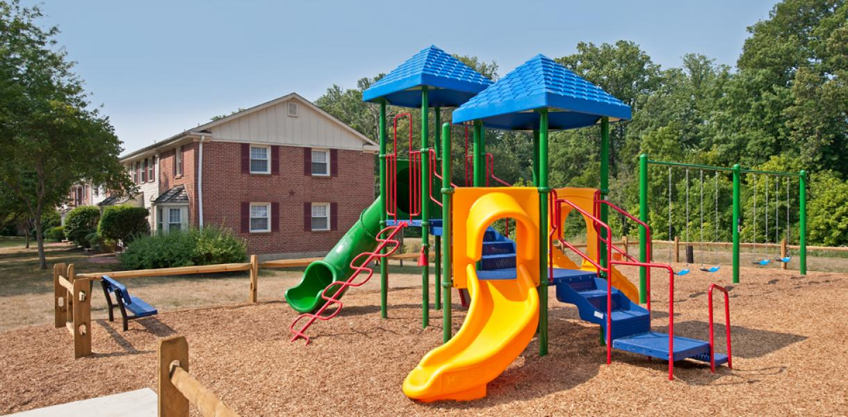 a photo of a colorful playground featured for the children that live within Greenville Place Apartments